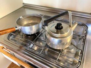 キッチン備え付けのやかんとなべがガスコンロに置いてある