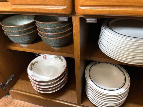 キッチン備え付けの食器棚にある丼やラーメン丼、カレー皿など